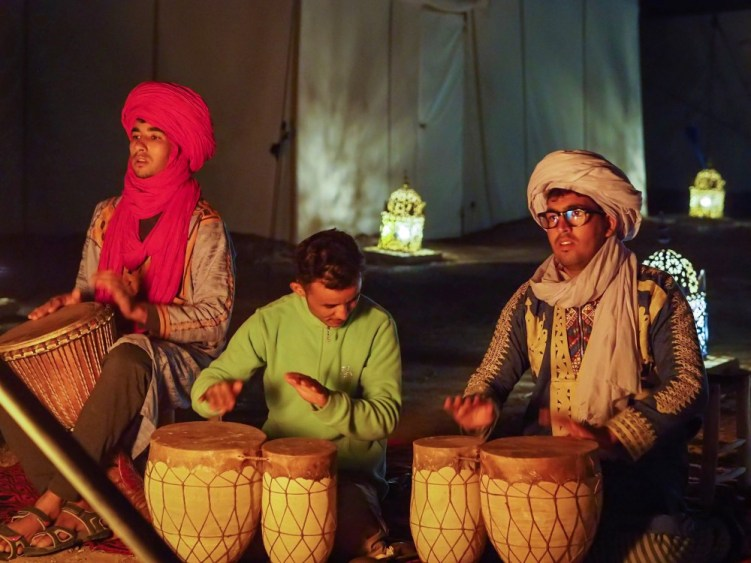 Berbers playing drums at a Sahara desert camp at night