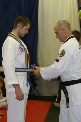 Photo of Adam Zwan receiving his latest Taekwondo belt.