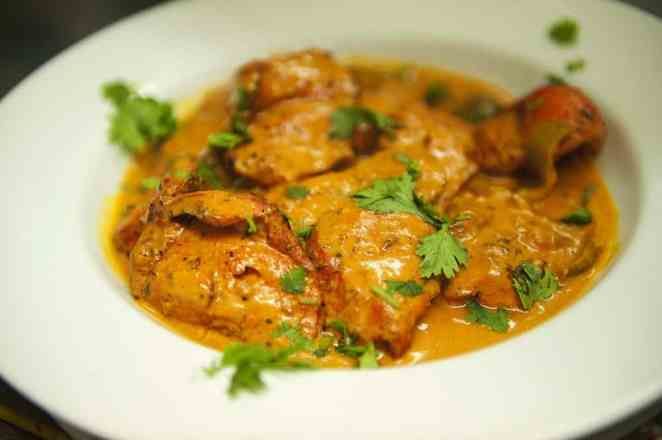 "TO GO WITH AFP STORY BY LUCIE GODEAU: A plate of Chicken Tikka Masala is pictured in the Shish Mahal restaurant in Glasgow, Scotland, on July 29, 2009. The Ali family, owners of Shish Mahal restaurant in Glasgow, claim to have come up with the creamy, mildly spicy curry in the 1970s to please the Scots, and which eventually become the most popular dish in British restaurants. ""Chicken tikka masala was invented in this restaurant, we used to make chicken tikka, and one day a customer said, 'I'd take some sauce with that, this is a bit dry',"" said Ahmed Aslam Ali, 64, founder of Shish Mahal. AFP PHOTO/Andy Buchanan (Photo credit should read Andy Buchanan/AFP/Getty Images)"