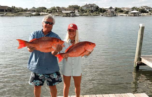Two people hold fish after deep sea fishing.
