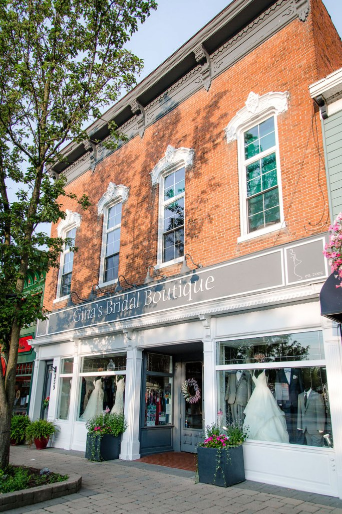 The exterior of a bridal shop with wedding dresses in the window.