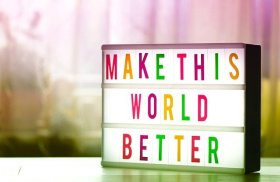 Coping with isolation - volunteer to feel more connected. Image of a lightbox with the message make the world a better place.