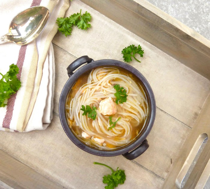 a bowl of noodle soup on a wooden tray