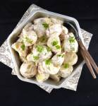 picture of potato salad in a silver dish with two brown spoons