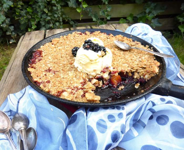 picture of an apple and blackberry dessert in a skillet with a blue scarf and tablespoons by the side