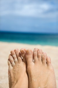 Woman's sandy feet on beach.