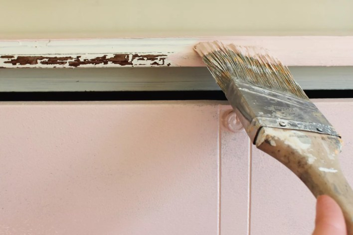 A paintbrush painting a dresser with pink chalk paint