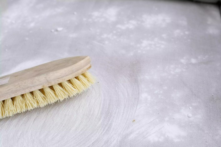using a bristle brush to work baking soda into the chair