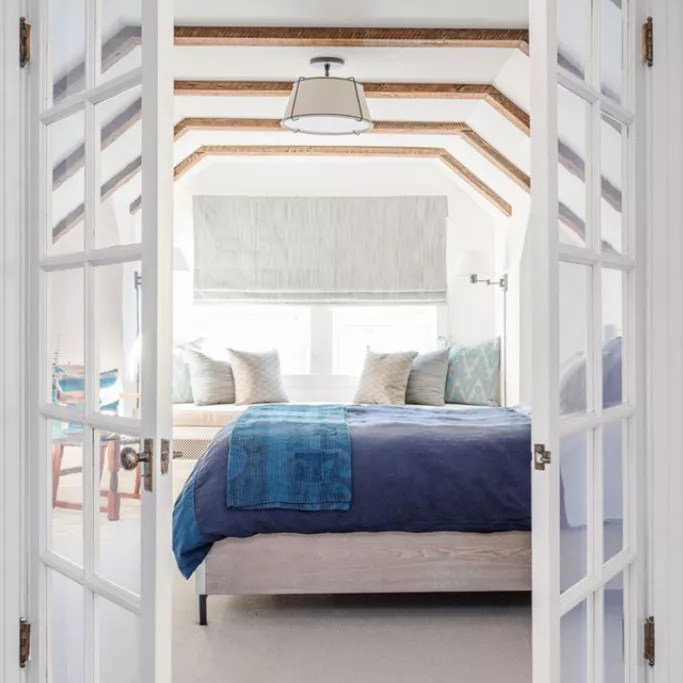 Renovated attic master bedroom with French doors and exposed beams.