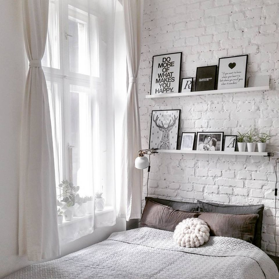 A bedroom with a white brick wall and shelves