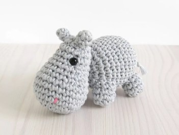 Small grey crochet hippo on white wood.