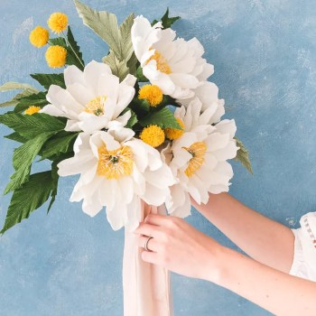 A woman holding a white and yellow paper flower bouquet