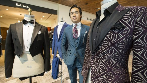 Michael Nguyen is framed by a selection from his Garrison line of tuxedo jackets, in the Holt Renfrew, Yorkdale Mall location. Nguyen has come full circle, for as a fashion-obsessed young stock boy he folded cashmere sweaters at Holt Renfrew. The upscale retailer now carries his expanding bespoke formal wear line.