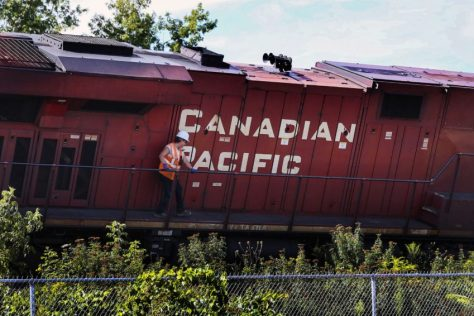 A worker grabs hold of the railing of a derailed CN engine near Bridgeman and Howland Aves. on August 21.
