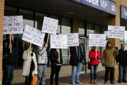 Migrants and their Canadian spouses caught up in the sponsorship backlog protested recently in front of Immigration Minister Chris Alexander's constituency office in Ajax.