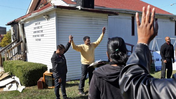 Pastor David Triggs and his wife Charronda hold hands and take part in the outdoor service following a fire at the New Life Missionary Baptist Church in St. Louis, one of a spate of church fires in the area in recent weeks.