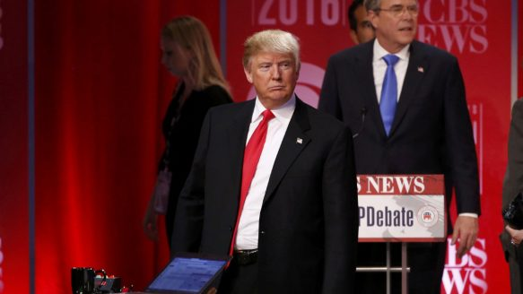 Republican U.S. presidential candidate and former Governor Jeb Bush (rear) walks past rival candidate businessman Donald Trump as he stands at the front of the stage at the conclusion of the Republican U.S. presidential candidates debate on February 13, 2016.