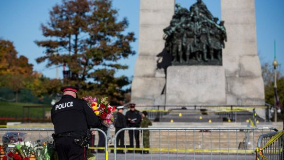 An Ottawa police officer lays flowers at the National War Memorial and pays his respects for Cpl. Nathan Cirillo of the Canadian Army Reserves, who was killed Wednesday by a gunman.