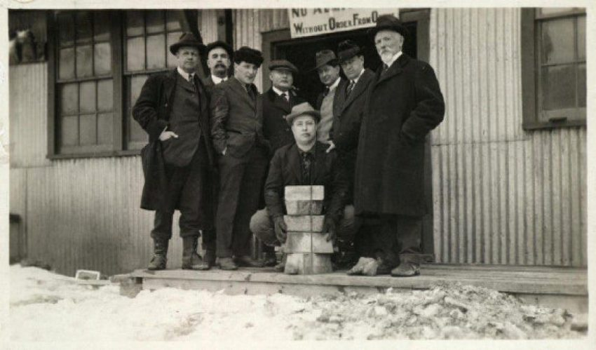 J.P. Bickell holds five gold bars while the McIntyre Mines' board of directors looks on.