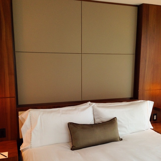 The Dux bed, Pratesi sheets, plenty of height, afternoon light, and a bedside notepad and pen.