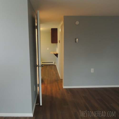 Apartment remodel hallway with grey paint and faux wood floor
