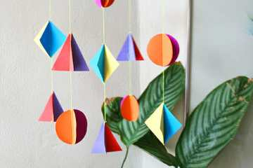 If you are looking for colorful geometric nursery mobile here is a super easy DIY.