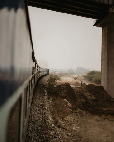 train sous un viaduc en Inde