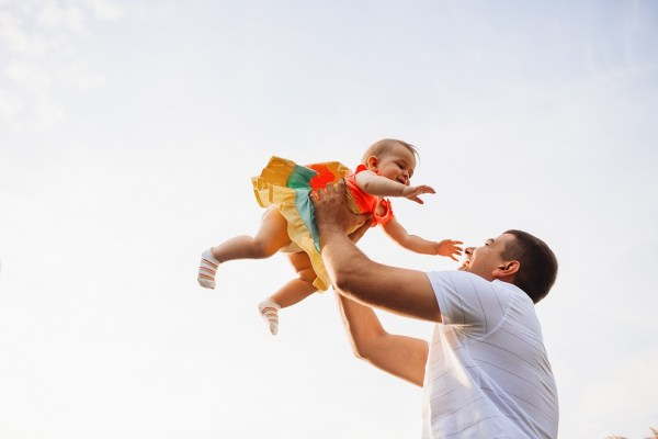 Happy father holds charming little girl up under summer sky