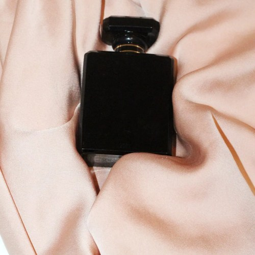 Bottle of perfume on pink silk background for blog on physical intimacy after infidelity