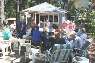 TOURS COMING UP - Lakewood Historical Society members touring Silcox Island recently learned about the island from Dorothy Holm, granddaughter of the original land purchaser, Alvert Silcox. Here part of the group of nearly 60 enjoys the shaded patio of the Holm house on the island before taking a guided tour of the 26 homes or cottages located on the 13=acre island.