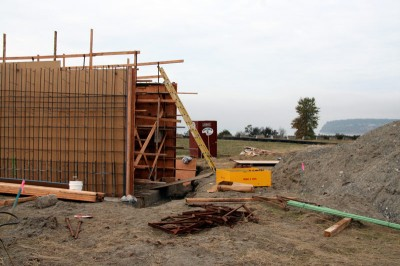 """The first bit of concrete for the 900+ foot long """"Bridge to the Beach"""" will be poured this week. The bridge will head southwest toward the water, then turn right about 90 degrees and come down near the tall tree in the background."""