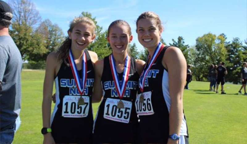 Three members of the girls Cross Country team show off their medals after a race.