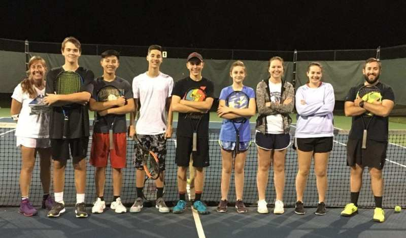 The boys and girls tennis team at The Summit stand together on the court with their coaches.