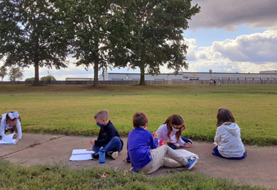 Summit students sit outside after school and write in notebooks.