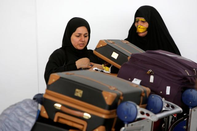 Women check their luggage after arriving on a flight to New York from Dubai