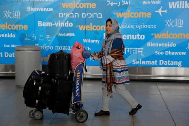 A woman exits immigration after arriving in New York from Dubai