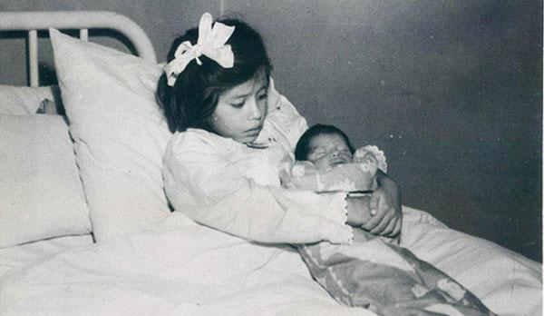 Five-year-old Lina Medina cradles her baby shortly after giving birth in Peru in 1939