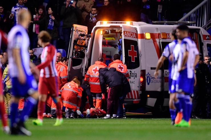 Antoine Griezmann watches on as Torres is put into the ambulance