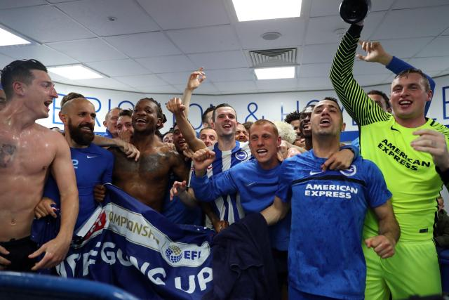 The Brighton team celebrate after making it into the Premier League
