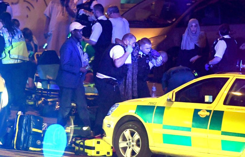 Police assist a woman caught up in the panic at Finsbury Park after reports a van was deliberately driven at pedestrians