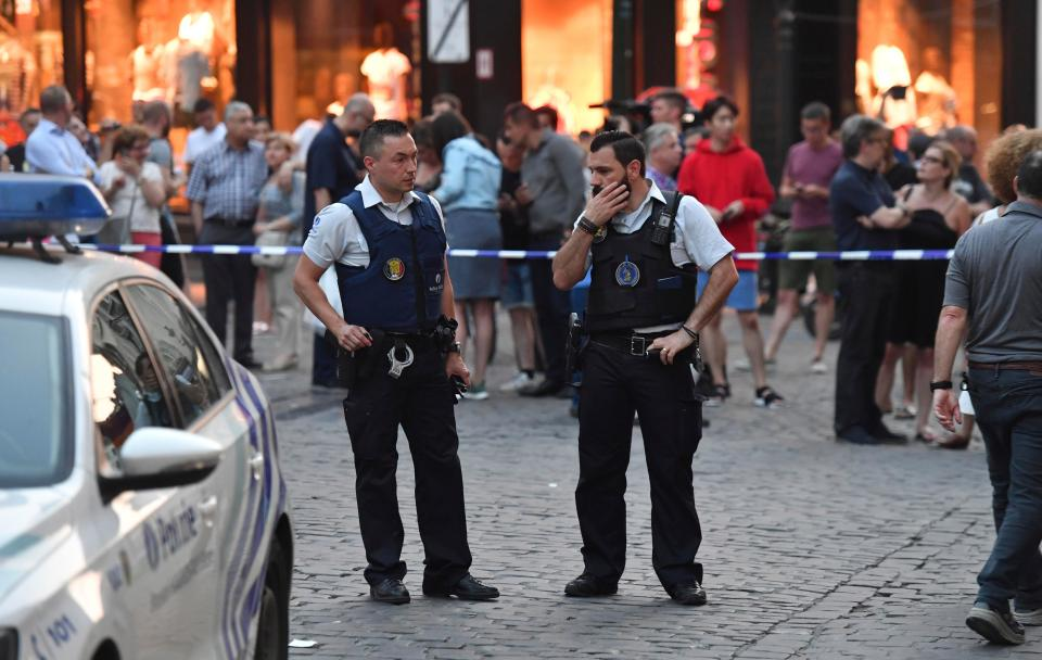 Belgian police stand in front of a police cordon as people are evacuated at the Grand Place square near Central Station