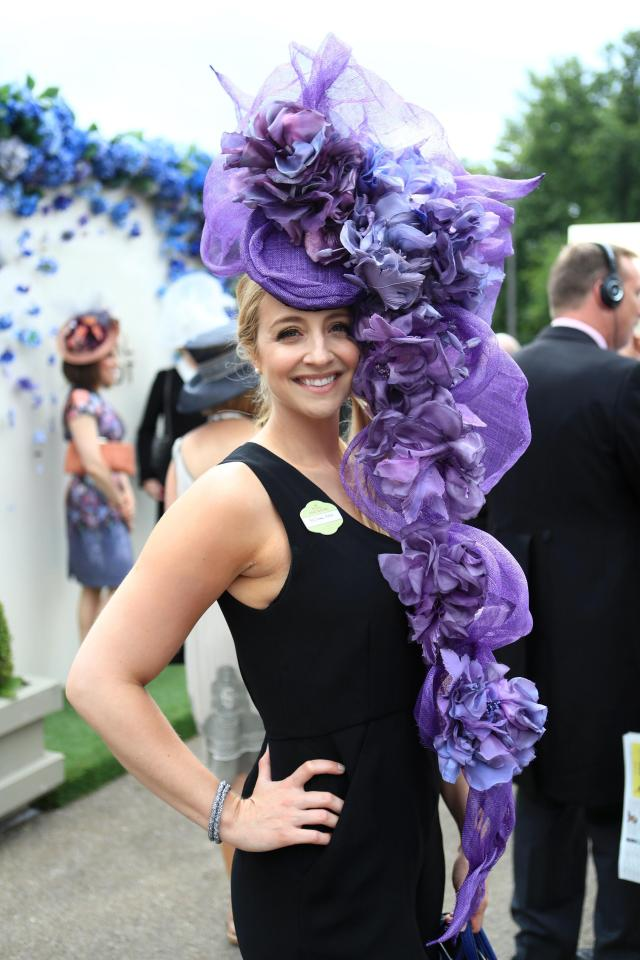 A pretty racegoer beamed as she posed for paps in a black strappy dress and her giant headwear, which featured cascading purple flowers