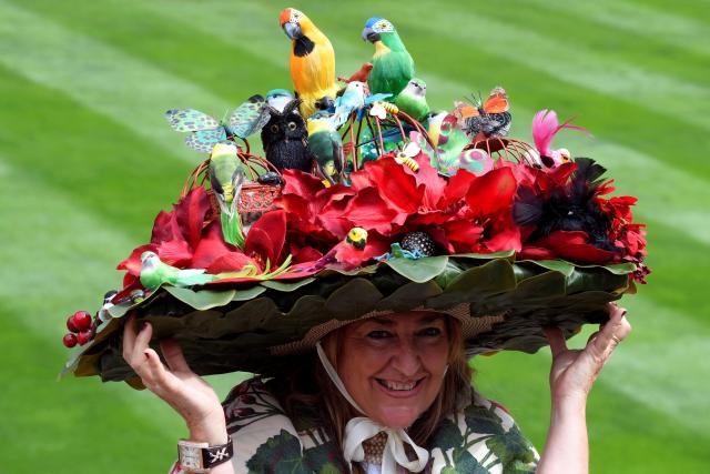 One reveller giggled while posing for the paps in her enormous headwear that featured a bed of flowers and colourful bird props