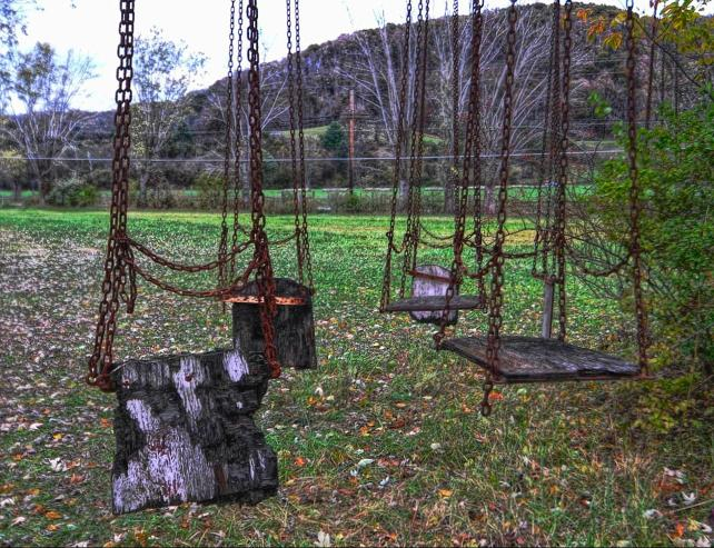 A rusted swing set in the abandoned Lake Shawnee Amusement park in West Virginia, USA. The derelict park sits on a site that has witnessed many terrible murders and is said to be haunted