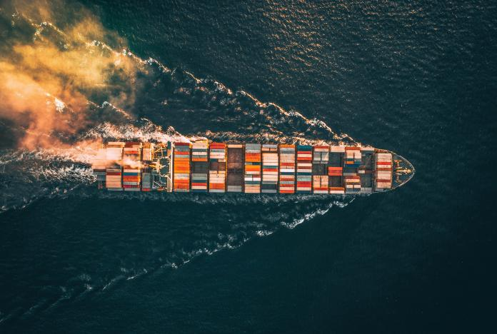 One of the beautiful drone shots show a colourful cargo ship sailing out to sea