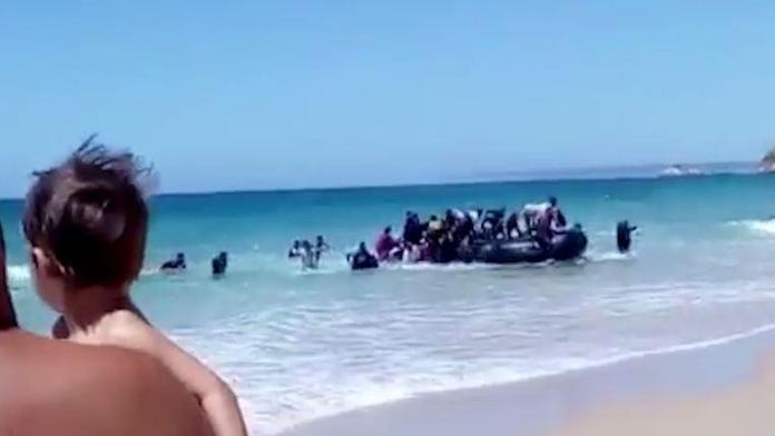 The men arrived on the beach in a black Zodiac inflatable as shocked tourists watched from the shore