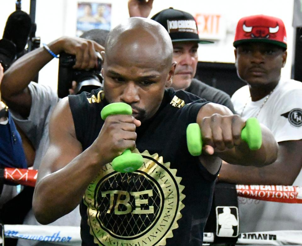 Floyd Mayweather practises his punching with weights in his hands
