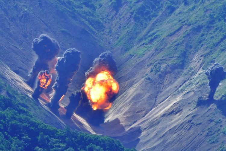 Explosions erupt on the mountain landscape after being peppered by the munitions