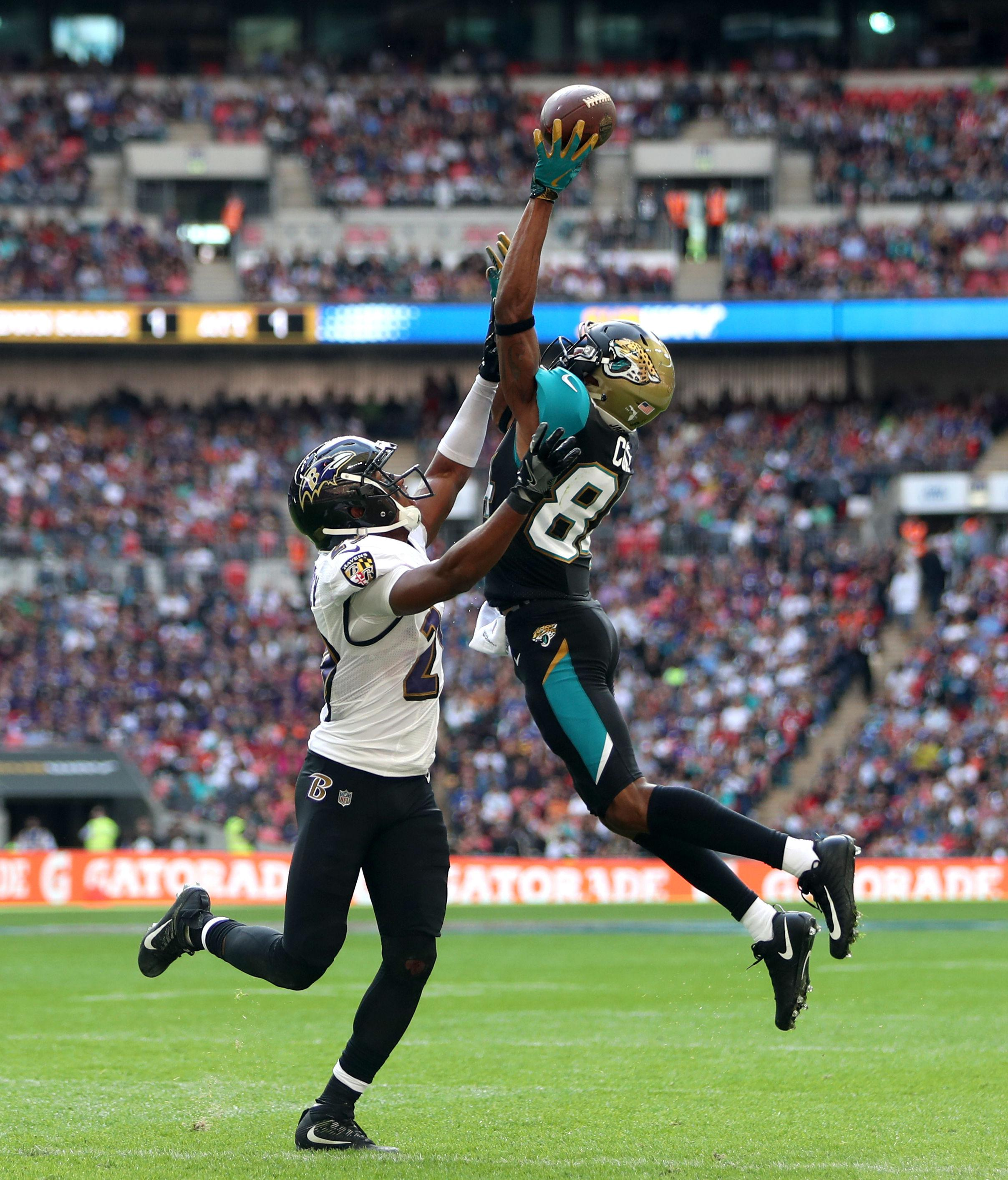 A receiver and a defensive back battle for the ball when it is thrown in the air