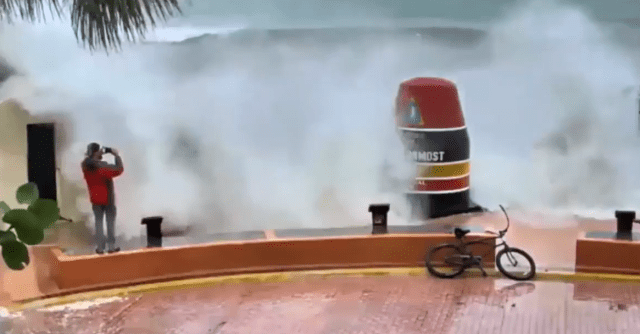 The man is pictured filming the colossal waves caused by Hurricane Irma in Key West,Florida